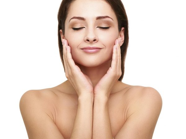 Beautiful spa woman with clean beauty skin touching her face with closed eyes. Beauty natural model